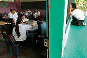A youngster who is not attending school looks through the classes window as students from the only school in Leones, Honduras share a single class for all grades.  Children from the ages of 6-12 share this class for their education high up on the mountain.  Over 94% of Honduran children are enrolled in school, yet only 40% actually complete their schooling.  Hounduras is considered the third poorest country in the Western Hemisphere (Haiti, Nicaragua). With over 50% of the population living below the poverty line and 28% unemployed, Hondurans frequently turn to illegal immigration as a solution to their desperate situation. The Department of Homeland Security has noted an 95% increase in illegal immigrants coming from Honduras between 2000 and 2009, the largest increase of any country.