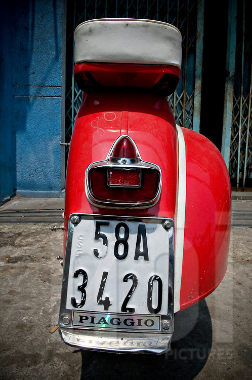 Vintage red vespa parked in a street of Ho Chi Minh city, Vietnam, Asia