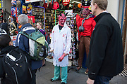 Man dressed in a horror face mask with a white coat and fake blood on Oxford Street, London, UK. Trying to tempt people into their souvenir and joke shop at Halloween.
