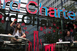 London, UK. 27th August, 2021. Environmental activists from Extinction Rebellion raise clenched fists after spreading blood-red paint across the facade of Standard Chartered bank during a Blood Money March through the City of London. Extinction Rebellion were intending to highlight the £23bn which they say Standard Chartered has invested in fossil fuels since the Paris Agreement whilst calling on the UK government to cease all new fossil fuel investment with immediate effect.