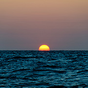 The sun disappears below the horizon over the Coral Sea. The frame is divided evenly between sky and water with the sun in the center. Taken at Swains Reef on the southern end of the Great Barrier Reef of the coast of Queensland, Australia.