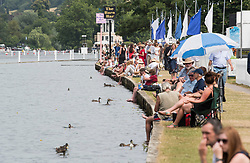 © Licensed to London News Pictures. 04/07/2018. Henley-on-Thames, UK. People enjoy the warm weather on the baks of the river on day one of the Henley Royal Regatta, set on the River Thames by the town of Henley-on-Thames in England. Established in 1839, the five day international rowing event, raced over a course of 2,112 meters (1 mile 550 yards), is considered an important part of the English social season. Photo credit: Ben Cawthra/LNP