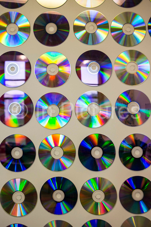 Multiple music compact disks hanging on a wall as part of a creative art display in the Royal Hospital for Neuro-disability, Putney, London, UK.