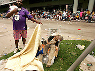 A man holding a baby uncovers the body of a dead man, suspected to have been sitting there for two days, outside the New Orleans Convention Center September 1, 2005. Several people among the thousands of stranded hurricane evacuees have died while waiting outside the building, with no sign of imminent help on the way.