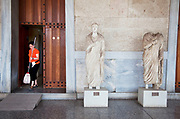 A cleaner carrying a mop beside ancient Greek statues at The Stoa of Attalos or Attalus located in the east side of archaeological site of the Ancient Agora in Athens just oposite the Adrianou street in Monastiraki. The Stoa of Attalos was built around 150 BC, by Attalos II, King of Pergamos as a donation to Athens. The construction of the building began in 159 BC and ended in 138 BC. The building was the largest in length in Greece during the antiquity. It was rebuilt in the same style and shape from 1953 to 1956 with beautifully crafted marble columns. It is recognised as one of the most impressive stoa in the Athenian Agora. Typical of the Hellenistic age, the stoa was more elaborate and larger than the earlier buildings of ancient Athens. The stoa's dimensions are 115 by 20 metres wide (377 by 65 feet wide) and it is made of Pentelic marble and limestone. The building skillfully makes use of different architectural orders. The Doric order was used for the exterior colonnade on the ground floor with Ionic for the interior colonnade. Athens is the capital and largest city of Greece. It dominates the Attica periphery and is one of the world's oldest cities, as its recorded history spans around 3,400 years. Classical Athens was a powerful city-state. A centre for the arts, learning and philosophy.