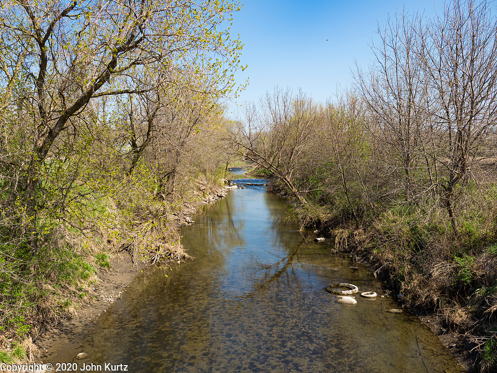 """26 APRIL 2020 - JEWELL, IOWA: An irrigation ditch that runs through Jewell. Jewell, a small community in central Iowa, became a food desert when the only grocery store in town closed in 2019. It served four communities within a 20 mile radius of Jewell. Some of the town's residents are trying to reopen the store, they are selling shares to form a co-op, and they hold regular fund raisers. Sunday, they served 550 """"grab and go"""" pork roast dinners. They charged a free will donation for the dinners. Despite the state wide restriction on large gatherings because of the COVID-19 pandemic, the event drew hundreds of people, who stayed in their cars while volunteers wearing masks collected money and brought food out to them. Organizers say they've raised about $180,000 of their $225,000 goal and they hope to open the new grocery store before summer.            PHOTO BY JACK KURTZ"""