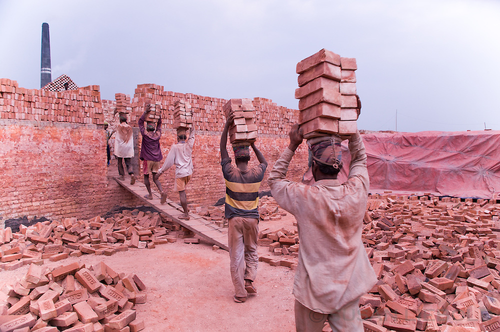 Men carry stacks of bricks on their heads to transport to another location at the brick making factory, Bangladesh.