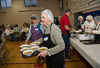 Marjory Wilkinson and Bo Fontaine are among the many volunteers who serve their guests during the Hands Across the Table dinner held at St Andre Bassette Parish Hall on Wednesday evenings.  (Karen Bobotas/for the Laconia Daily Sun)