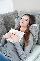 Portrait of young woman with opened book sleeping on couch at home