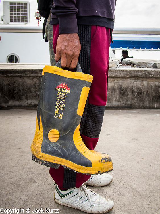 02 AUGUST 2013 - KOH SAMET, RAYONG, THAILAND:  A volunteer on the Ban Phe municipal pier holds his boots while he waits for a boat to take him to Koh Samet island so he can help cleanup fouled beaches on the island. About 50,000 liters of crude oil poured out of a pipeline in the Gulf of Thailand over the weekend authorities said. The oil made landfall on the white sand beaches of Ao Prao, on Koh Samet, a popular tourist destination in Rayong province about 2.5 hours southeast of Bangkok. Workers from PTT Global, owner of the pipeline, up to 500 Thai military personnel and volunteers are cleaning up the beaches. Tourists staying near the spill, which fouled Ao Prao beach, were evacuated to hotels on the east side of the island, which was not impacted by the spill. Officials have not said when Ao Prao beach would reopen. PTT Global Chemical Pcl is part of state-controlled PTT Pcl, Thailand's biggest energy firm.   PHOTO BY JACK KURTZ