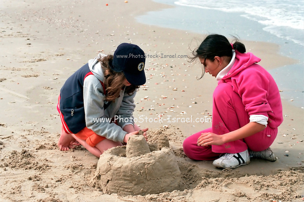 Israel, Tel Aviv, children aged 10, building a sand castle on the beach on a sunny day in winter