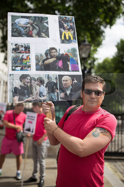 """© Licensed to London News Pictures . 10/08/2013 . London , UK . A protester with a placard with images of violence against gay people overlaid with the logos of Sochi Olympic Games sponsors , which are due to be held in Russia in 2014 . Demonstration against homophobic laws being enacted in Russia on Whitehall this afternoon (10th August 2013) . Legislation includes banning gay pride events for100 years , banning the distribution of """" propaganda of non-traditional sexual relations """" to minors , making it illegal for the adoption of Russian children by gay couples or any single person who comes from a country that recognises marriage equality and giving authorities the rights to arrest foreign nationals whom they suspect are LGBT or pro gay with the right to detain them for up to 14 days. Photo credit : Joel Goodman/LNP"""