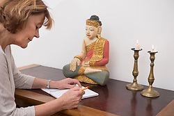 Senior woman writing in notebook, Buddha statue and candles in the background, Munich, Bavaria, Germany