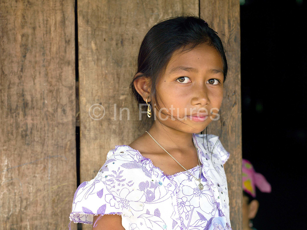 Portrait of a Hmong girl outside her home, Ban Chalern, Phongsaly province, Lao PDR. The remote and roadless village of Ban Chalern is situated along the Nam Ou river (a tributary of the Mekong) and will be relocated due to the construction of the Nam Ou Cascade Hydropower Project Dam 7. The Nam Ou river connects small riverside villages and provides the rural population with food for fishing. But this river and others like it, that are the lifeline of rural communities and local economies are being blocked, diverted and decimated by dams. The Lao government hopes to transform the country into 'the battery of Southeast Asia' by exporting the power to Thailand and Vietnam.