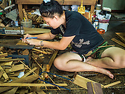 02 NOVEMBER 2016 - BANGKOK, THAILAND: GOB, who now runs the family spirit house workshop, uses small table saw to cut teak wood for a spirit house. There used to be 10 families making traditional spirit houses out of teak wood in Ban Fuen, a community near Wat Suttharam in the Khlong San district of Bangkok. The area has been gentrified and many of the spirit house makers have moved out, their traditional wooden Thai houses replaced by modern apartments. Now there is just one family making the elaborate spirit houses. The spirit houses are made by hand. It takes three days to make a small one and up to three weeks to make a large one. Prices start at about $90 (US) for a small one. The largest, most elaborate ones can cost over $1,000 (US). Almost every home and most commercial buildings in Thailand have a spirit house, which is a shrine to the protective spirit of a the land. Spirit houses are also common in Burma, Cambodia, and Laos.        PHOTO BY JACK KURTZ