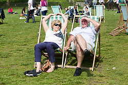 © Licensed to London News Pictures. 12/05/2016. LONDON, UK.  A couple relax on deckchairs in Green Park during warm sunny weather at lunchtime.  Photo credit: Vickie Flores/LNP