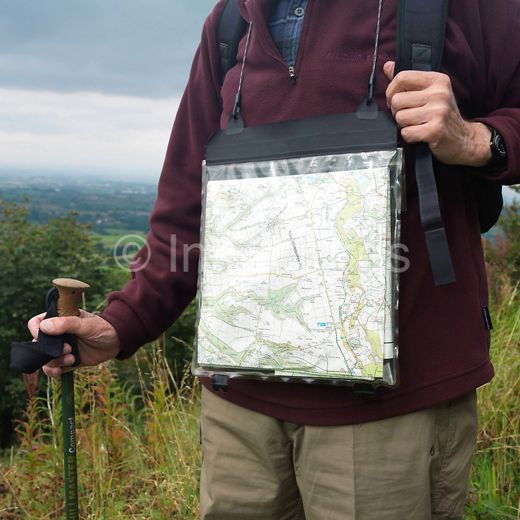 A male hiker with a walking pole wears a plastic case with a map inside at Sutton Bank, North York Moors, North Yorkshire, UK