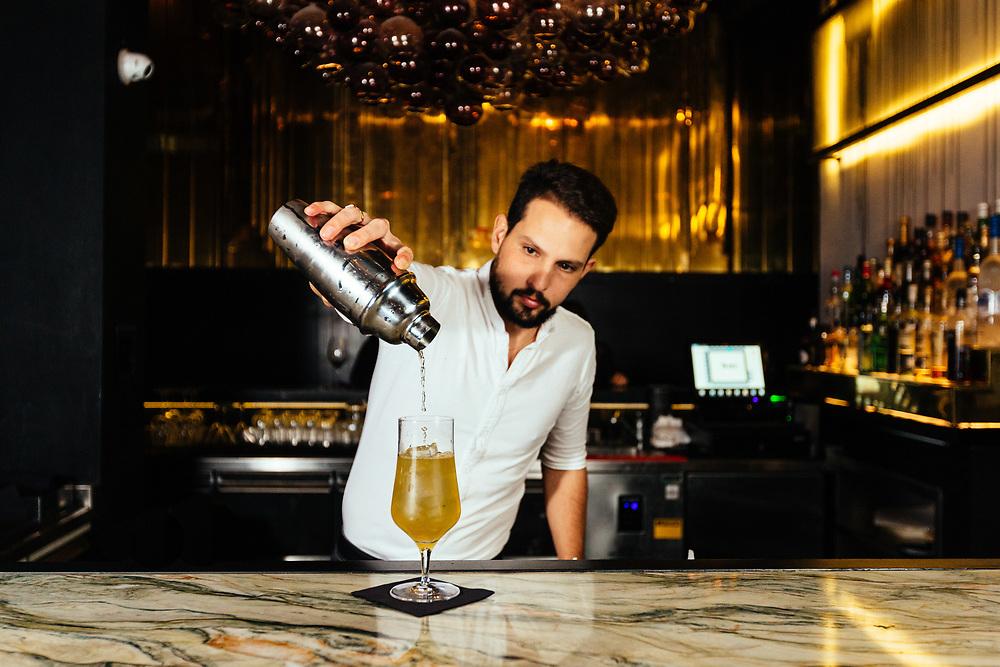 Bartender and co-owner Ron Ben Yair preparing a cocktail containing Grey Goose vodka stirred with lime, elderflower, lemonade, and freshly-snipped basil (name not disclosed) at Bakshish Bar at Mahane Yehuda Market, often called 'The Shuk'  in Jerusalem, Israel, on November 21, 2017.