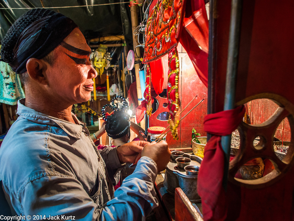"""18 AUGUST 2014 - BANGKOK, THAILAND: A  member of the Lehigh Leng Kaitoung Opera troupe prays backstage before a performance at Chaomae Thapthim Shrine, a small Chinese shrine in a working class neighborhood of Bangkok. The performance was for Ghost Month. Chinese opera was once very popular in Thailand, where it is called """"Ngiew."""" It is usually performed in the Teochew language. Millions of Chinese emigrated to Thailand (then Siam) in the 18th and 19th centuries and brought their culture with them. Recently the popularity of ngiew has faded as people turn to performances of opera on DVD or movies. There are still as many 30 Chinese opera troupes left in Bangkok and its environs. They are especially busy during Chinese New Year and Chinese holiday when they travel from Chinese temple to Chinese temple performing on stages they put up in streets near the temple, sometimes sleeping on hammocks they sling under their stage. Most of the Chinese operas from Bangkok travel to Malaysia for Ghost Month, leaving just a few to perform in Bangkok.     PHOTO BY JACK KURTZ"""