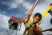 Children playing on a PlayPump near Pretoria, South Africa. The PlayPump Water System uses the energy of children at play to operate a water pump. It is manufactured by the South African company Roundabout Outdoor. It operates in a similar way to a windmill-driven water pump. The PlayPump water system is a like a playground merry-go-round attached to a water pump. The spinning motion pumps underground water into a 2,500-liter tank raised seven meters above ground. The water in the tank is easily dispensed by a tap valve. According to the manufacturer the pump can raise up to 1400 liters of water per hour from a depth of 40 meters. Excess water is diverted below ground again. The storage tank has a four-sided advertising panel. Two sides are used to advertise products, thereby providing money for maintenance of the pump, and the other two sides are devoted to public health messages. There are more than 1000 PlayPump systems in five countries of Sub-Saharan Africa, providing clean drinking water to more than 1 million people in need.