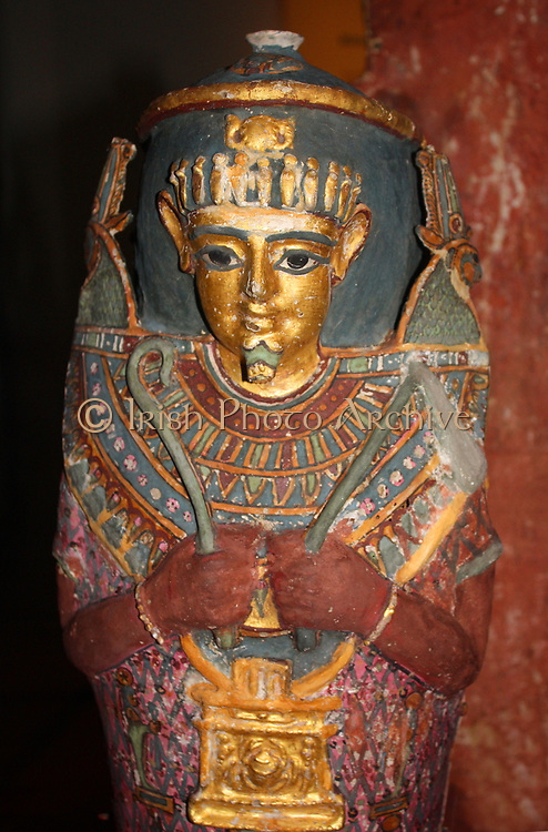 Painted and gilded mummy case of an infant. The constructional details of this case are not fully visible, but the materials used included linen and plant fibre. A painted bead-net on a pink background imitates the garment often shown worn by Osiris.