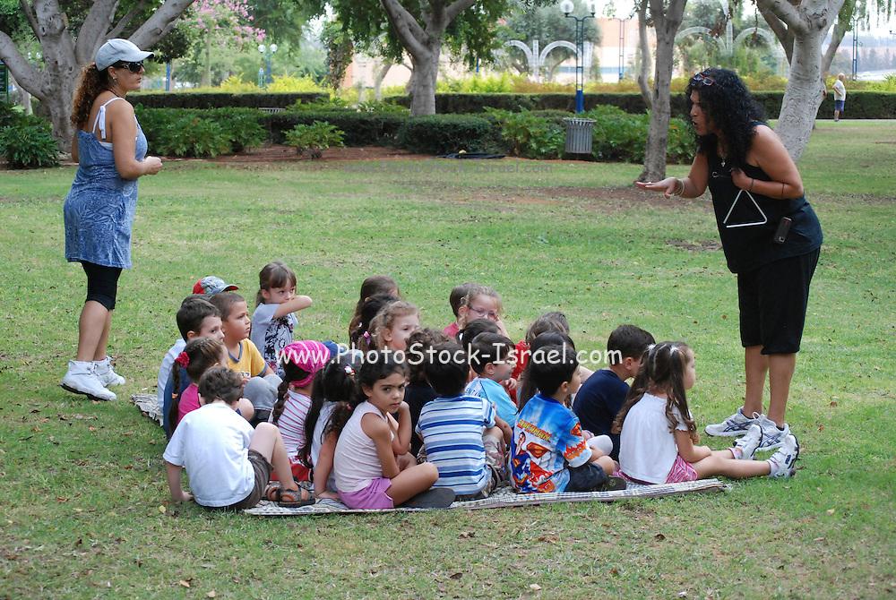 Israel, Preschool teacher with a group of preschool children in a park