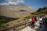 A memeber of the mountain rescue team explaining to a group of tourists the new crack in the mountain near Castelluccio that has been opened by the earthquake