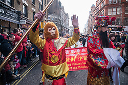 © Licensed to London News Pictures. 14/02/2016. London, UK.   A man dressed as a monkey accompanies a man dressed as Money God, as the Chinese New Year parade take place around Chinatown celebrating the Year of the Monkey. Photo credit : Stephen Chung/LNP