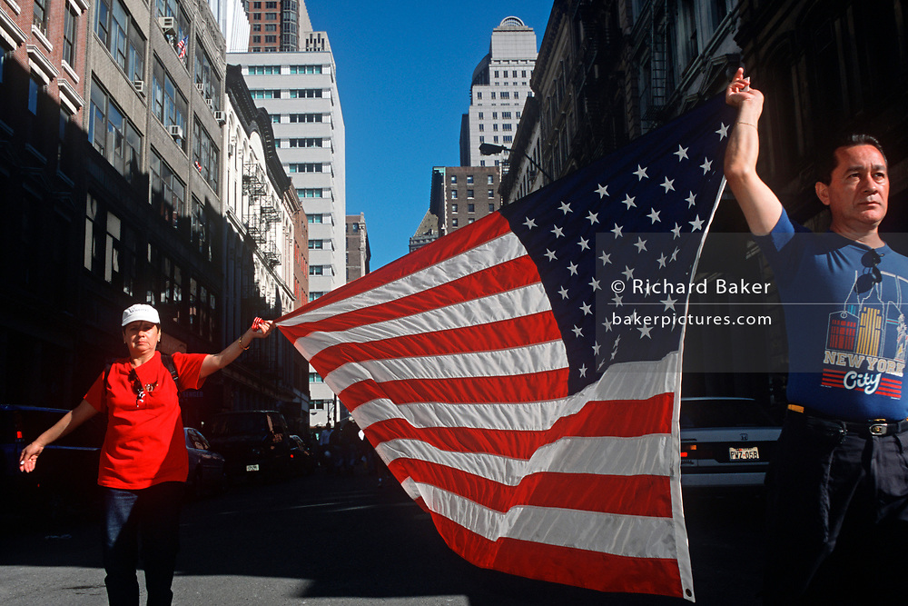 A week after the 9-11 terrorist attacks on the Twin Towers and the Pentagon, a couple cary the American flag down a lower-Manhattan street, on 21st September 2001, New York, USA. (Photo by Richard Baker / In Pictures via Getty Images)