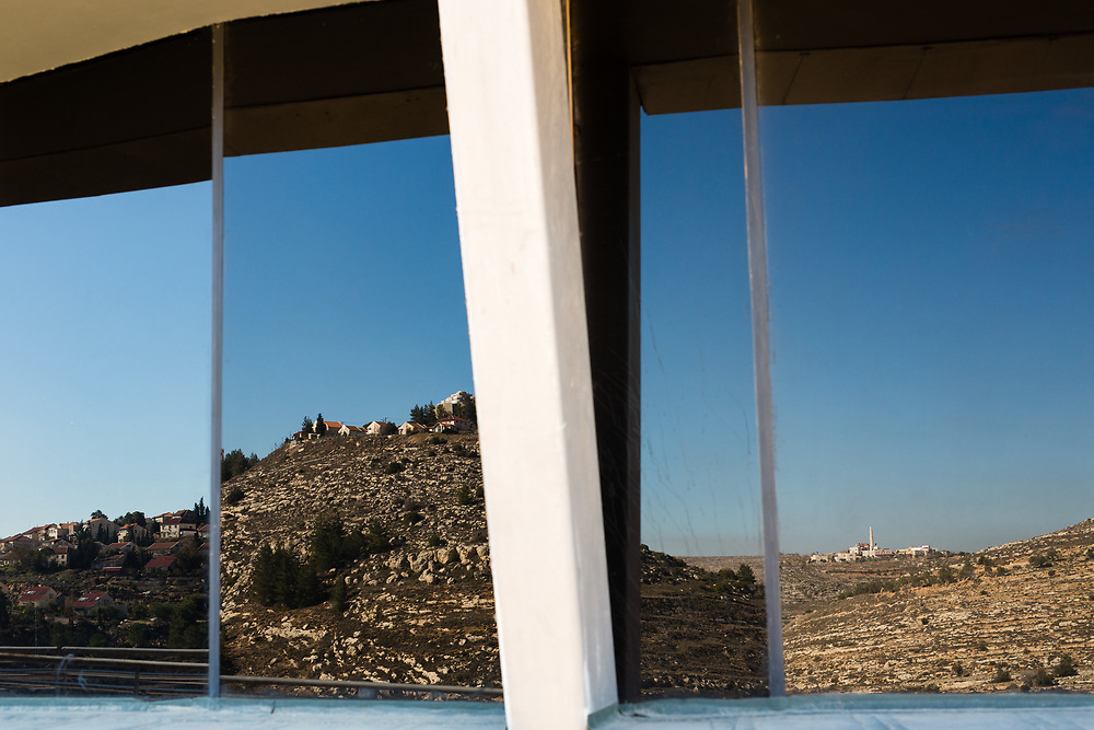 The West Bank Jewish settlement of Shiloh (L), and a nearby Palestinian village (R), are reflected in the windows of the lookout tower at the archaeological park of Ancient Shiloh, which is located at the entrance to the modern Jewish settlement of Shiloh, south of the Palestinian West Bank town of Nablus, on January 1, 2017. Shiloh was the religious capital of Israel, an assembly place for the people of Israel and a center of worship before the first temple was built in Jerusalem. Its sacred area housed the Ark of Covenant.