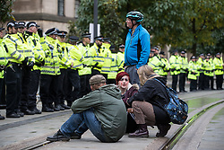 © Licensed to London News Pictures . 01/10/2017. Manchester, UK. Anti Tory protesters block tramtracks leading to the network having to halt services at St Peter's Square opposite the Midland Hotel . People take part in a demonstration against the Conservative Party in Manchester during the Conservative Party Conference , which is taking place at the Manchester Central Convention Centre . Photo credit: Joel Goodman/LNP