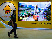 "23 FEBRUARY 2016 - BANGKOK, THAILAND:   A man walks by a Nok Air electronic billboard in the domestic terminal at Don Mueang Airport. Nok Air, partly owned by Thai Airways International and one of the largest and most successful budget airlines in Thailand, cancelled 20 flights Tuesday because of a shortage of pilots and announced that other flights would be cancelled or suspended through the weekend. The cancellations came after a wildcat strike by several pilots Sunday night cancelled flights and stranded more than a thousand travelers. The pilot shortage at Nok comes at a time when the Thai aviation industry is facing more scrutiny for maintenance and training of air and ground crews, record keeping, and the condition of Suvarnabhumi Airport, which although less than 10 years old is already over capacity, and facing maintenance issues related to runways and taxiways, some of which have developed cracks. The United States' Federal Aviation Administration late last year downgraded Thailand to a ""category 2"" rating, which means its civil aviation authority is deficient in one or more critical areas or that the country lacks laws and regulations needed to oversee airlines in line with international standards.       PHOTO BY JACK KURTZ"