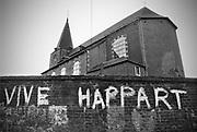 Belgie, Fourons, 30-5-1988Leus op de muur van het kerkhof en de kerk in Voeren in de Voerstreek vlak over de grens met Nederland onder Zuid Limburg.Happart was de burgemeester van deze gemeente en onderwerp in de taalstrijd die hier gevoerd werd. Hij was Franstalig en ondaks toezeggingen weigerde hij Vlaams, Nederlands te leren of spreken.Er waren regelmatig geweldadige confrontaties in de gemeente, maar Happart werd uiteindelijk afgezet.De gemeente grenst in het noorden aan Nederlands Limburg en in het zuiden aan de Waalse provincie Luik, maar nergens aan de rest van Vlaanderen. Het gebied dat deze gemeente omvat is in het Nederlandse taalgebied beter bekend onder de naam Voerstreek. Foto: Flip Franssen/Hollandse Hoogte
