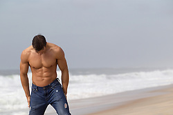 sexy man without a shirt in wet jeans at the beach in the hamptons
