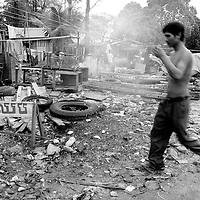 Man walks by trash heap in small fishing village outside of Sihanoukville, Cambodia