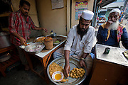 A man prepares food in a small restaurant in the old city of Dhaka, Bangladesh. Nearly 20 percent of Dhaka's more than seven million residents live in the slums.