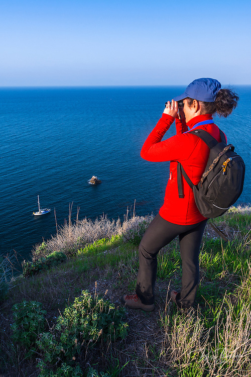 Hiker whale watching above Scorpion Cove, Santa Cruz island, Channel Islands National Park, California