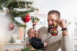 Portrait of father holding baby boy and bauble