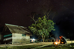 NO WEB/NO APPS - Exclusive. (Text available) A man makes a fire next to his house neath the starry sky, in 'Palma Real' native community, near Puerto Maldonado, Peru on July 17, 2017. The Amazon rainforest is famous as 'The Lung of the Earth', but also for the presence of numerous native communities, who have always lived isolated and in close contact with nature for generations, used to seek for food and medicines and to build items directly from the environment in which they live. The unstoppable rise of globalization has drastically changed their needs, expectations and consequently their way of life. Located in the Tambopata National Reserve, on the border between Peru and Bolivia, the native Comunidad Palma Real is one of the clearest examples of this change. Living on the banks of the Madre de Dios River since approximately 1976, Palma Real comprises about 300 people part of the nomadic community Ese-Eja, established in the Amazon rainforest of Peru before the Spanish colonization. Photo by Giacomo d'Orlando/ABACAPRESS.COM