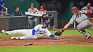 Kansas City Royals center fielder Michael A. Taylor (2) slides around the tag of Cincinnati Reds catcher Tyler Stephenson (37) to tie the game during the ninth inning at Kauffman Stadium.