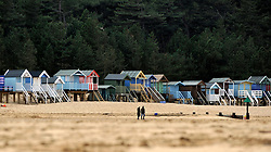 © Licensed to London News Pictures. 07/04/2012. Stiffkey, UK A couple walk along a deserted beaches lined with beach huts. People walk along quiet beaches at Holkham Bay, Norfolk today 7th April 2012.  Weather is expected to deteriorate oner the next two days Photo credit : Stephen Simpson/LNP