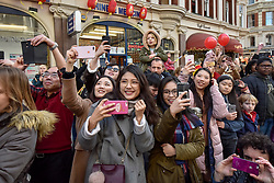 © Licensed to London News Pictures. 18/02/2018. LONDON, UK.  Members of the public photograph the Chinese New Year celebrations in Chinatown welcoming the Year of the Dog as a parade featuring dragon and lion dancers and traditional costumed characters pass by.  Chinese New Year in the capital draws hundreds of thousands of Londoners and tourists to enjoy the festivities and is the biggest such celebration outside Asia.  Photo credit: Stephen Chung/LNP