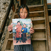 Soname shows a studio portrait of her her and her brother striking a pose and wearing Bhutan's national dress. Life at Mr and Ms Wangchuk's house on the edge of the Laya village.