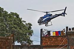 Helicóptero da polícia militar sobrevoa a favela Morro do Alemão em 29 novembro de 2010 no Rio de Janeiro, Brasil. A polícia vasculhou os esgotos em favelas do Rio de Janeiro segunda-feira por centenas de traficantes de drogas que fugiram de um ataque militar sem precedentes sobre as favelas cariocas que rendeu 40 toneladas de entorpecentes, mas poucas prisões. FOTO: Jefferson Bernardes/Preview.com