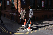 Two male pedestrians walk past a broken post that leans over after being pushed over by an unknown vehicle. Walking along the narrow pavement, one allows his older colleague to go ahead, so tight is the space. Heading out into sunlight, they carry on their journey on a warm lunchtime in the London borough of Southwark. The repairs appear to be imminent as the two cones, mark the place of damaged street items that protect the corner and building. Southwark is responsible for road works within its region of south London.