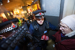 © Licensed to London News Pictures . 08/12/2012 . Manchester , UK . Police eject protesters after a number forced their way in to the branch . UKUncut hold a demonstration against corporate tax avoidance outside a branch of Starbucks on St Ann's Square in Manchester City Centre today (8th December 2012) . Photo credit : Joel Goodman/LNP