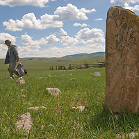 MONGOLIA. Smithsonian Museum archaeology team studies 2700+ year-old,  khirigsur burial mound at site near Lake Erkhel & Muren, Mongolia.  An ancient Deer Stone stands in foreground (from same era).<br /> <br /> MS0702_060701_0017.NEF