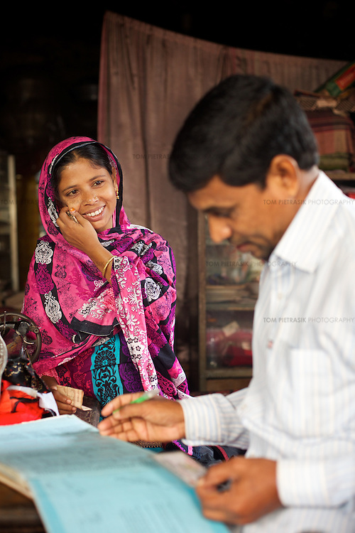 """Jahanara signs up for a micro credit scheme with an agent. She will borrow Tk20,000 that will be invested in the purchase of building tools that she will rent out. <br /> <br /> Jahanara works as a tailor to supplement her husband's income as a construction worker. She volunteers for NGO forum as a health and hygiene promoter working with female adolescents in the slum. A passionate advocate of hand-washing to both adults and children, she's seeing the result of her efforts: """"I like doing the work that I do, the fact that people can stay healthy. I like the result of my work."""" She's also involved in promoting drain clearing. """"Before, the latrines and drains were very dirty. Now, it's a lot better but there's so much more to do."""" <br /> <br /> Jahanara Akhter, age 27, is a resident of 36 Bari Colony, a slum in Mymensingh. Oxfam are working with partners NGO Forum to support residents of 36 Bari Colony in health promotion and disaster preparedness.<br /> <br /> Photo: Tom Pietrasik<br /> Mymensingh, Bangladesh<br /> November 19th 2014"""