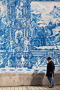 Man with walking cane passes azulejos Portuguese blue and white wall tiles of Capela das Almas de Santa Catarina  - St Catherine's Chapel in Porto, Portugal
