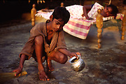 Korlap Rao (8) sweeps the floor whilst his mother, Narayamma (40) lies on a charpoy. She has AIDS and his father has fled. Kasapatanan  village, Araku valley, Andhra Pradesh, India